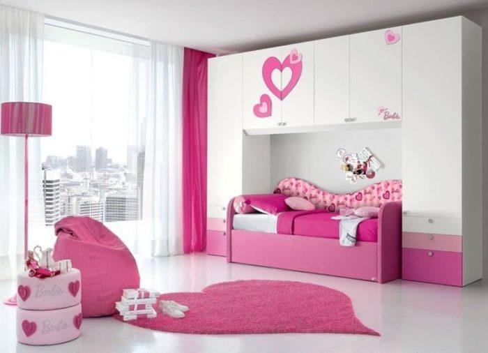 غرفة نوم باللون الابيض والبينك مع وسادة ضخمة أو مايسمي بالبوف تعطي منظراً جميلاً ومريحة جداً للاطفال
