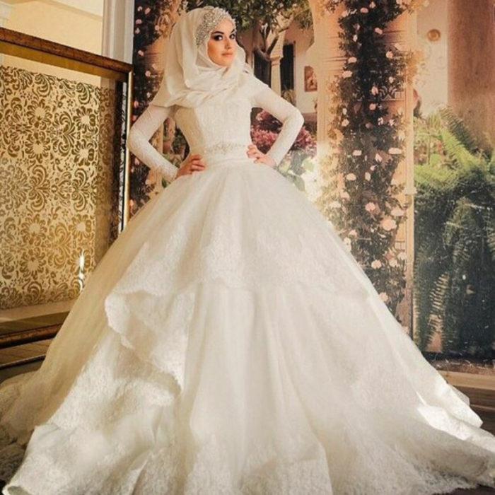 فستان منفوش بتصميم حلو جداً مع حزام على الوسط من الفصوص اللامعة مع لفة طرحة جرئية مطرزة من علي الرأس