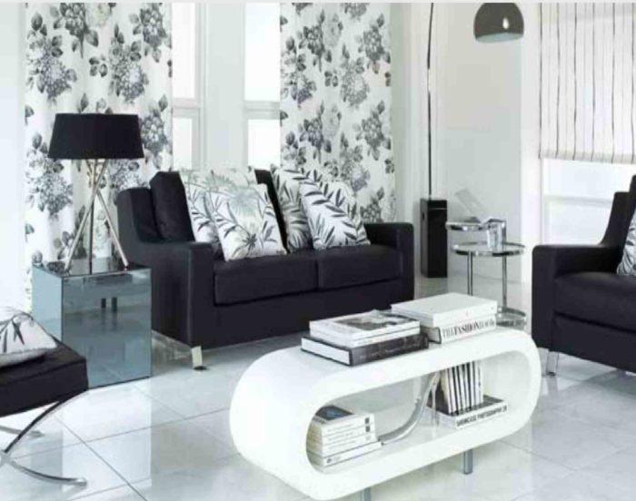 غرفة جلوس بتصميم جميل وجديد تحتوي على كنبة و2 كرسي سادة باللون الاسود مع وسائد مشجرة