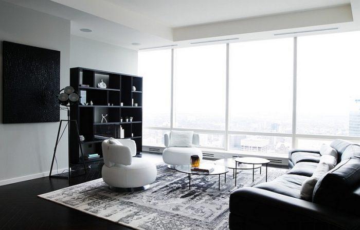 غرفة معيشة تحتوي كنبة مستديرة بتصميم مختلف وكراسي دائري باللون الابيض مع كتبة بتصميم هادئ جداً وشيك