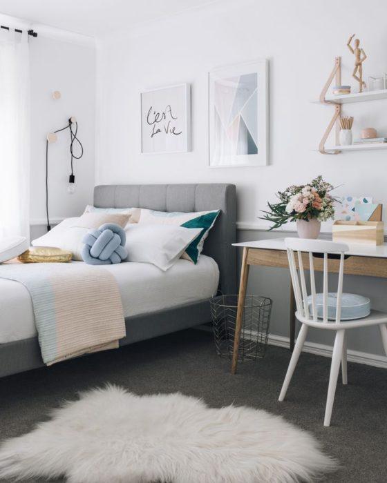 غرفة نوم بتصميم روعة وتتكون من سرير رمادي اللون وترابيزة مع كرسي صغير باللون الابيض