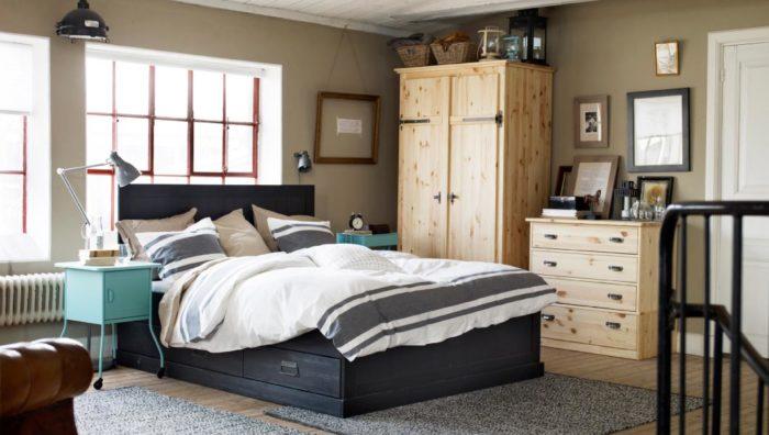 غرفة نوم بسيطة جداً وجميلة وتحتوي عل سرير باللون الاسود ودولاب صغير خشبي