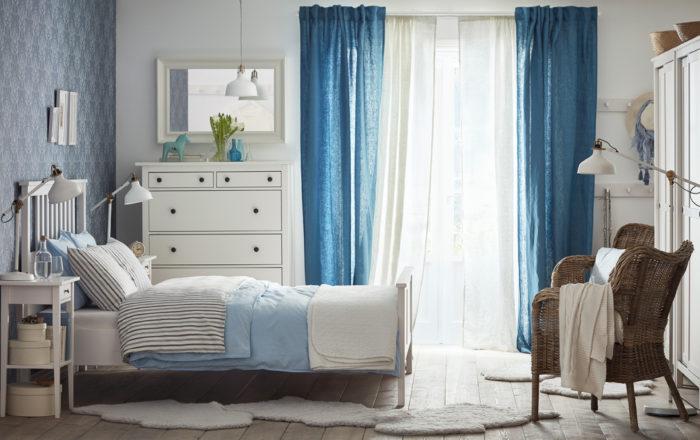 غرفة نوم رائعة وبسيطة حيث تحتوي على ستارة هادئة باللون الابيض والازرق وسرير وكمودينو بتصميم مختلف وجديد