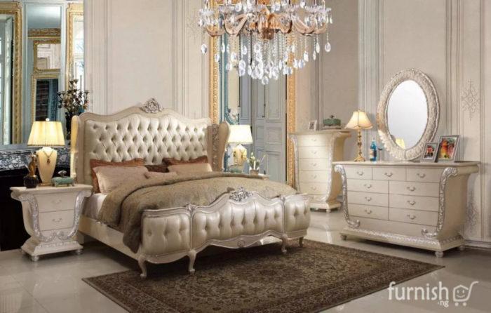 غرفة نوم شيك جداً لها طابع عصري حيث تحتوي على سرير فخم جداً باللون الدهبي مع نجفة متدلية من الكريستال