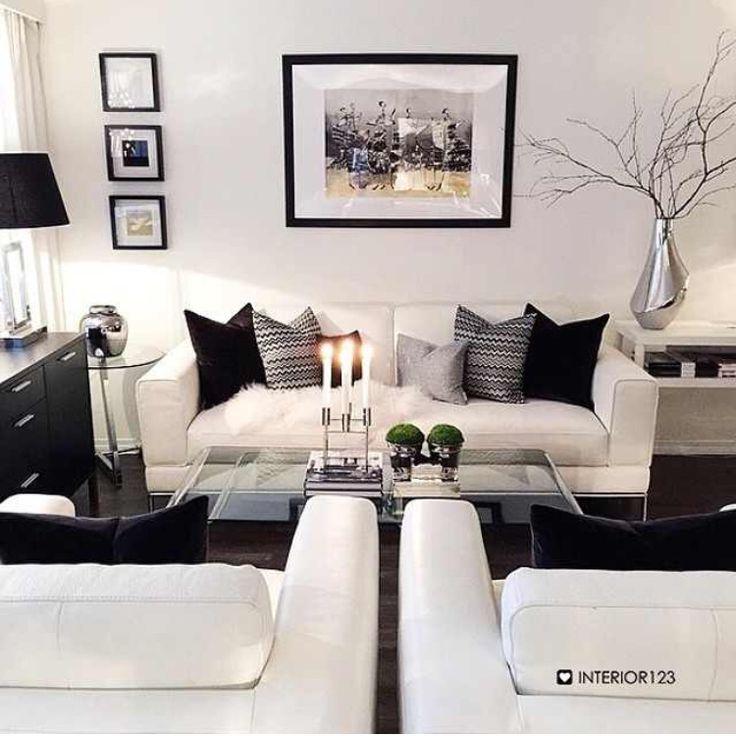 غرف معيشة تحتوي على كنبة و2 كرسي باللون الابيض مودرن مع وسائد صغيرة الحجم باللون الاسود السادة والجريه السادة مع والمنقوش مع طاولة زجاجية