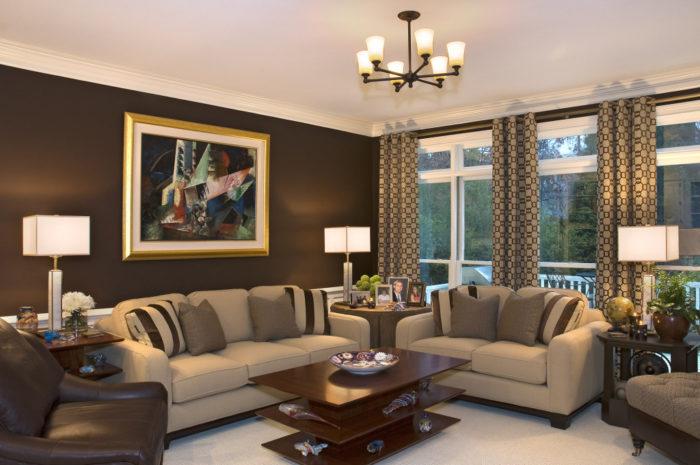 غرفة معيشة تتكون من أنتريه باللون البيج والبني مع ستائر بلاك أوت منقوشة وترابيزة خشب بنية اللون