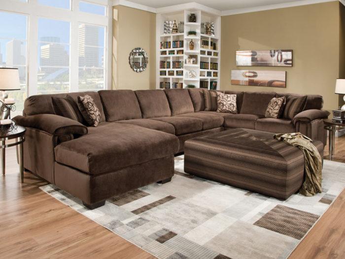 غرفة معيشة شيك جداً ورائعة تتكون من ركنة بنية اللون وسجادة مودرن بسيطة
