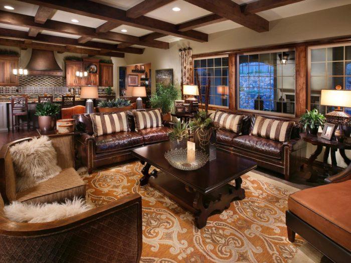 غرفة معيشة غيرتقليدية تتكون من 2 كنبة جلد باللون البني مع 2 كرسي باللون البيج وترابيزة خشبية رائعة