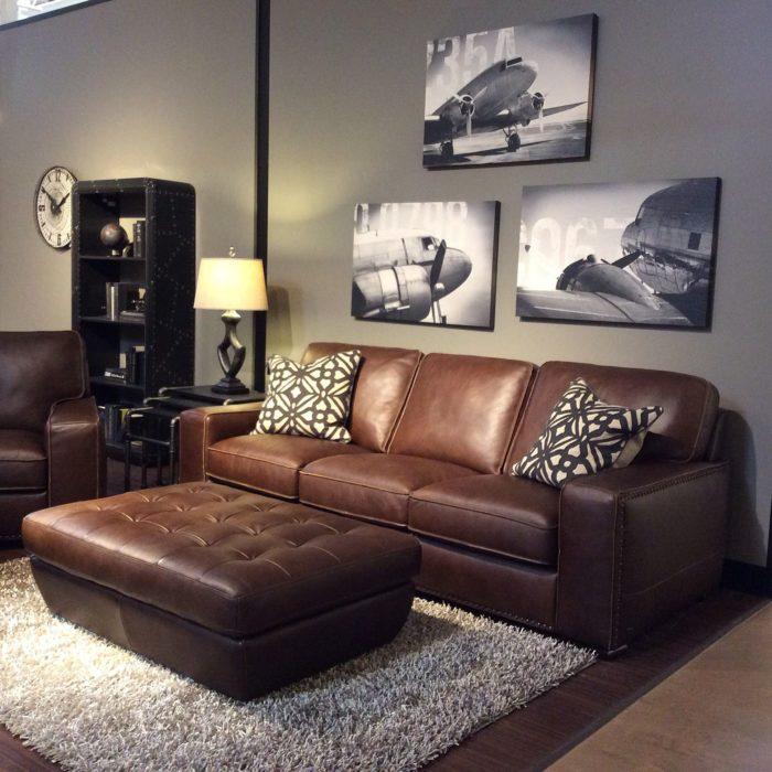 غرفة معيشة مكونة من كنبة جلد وكرسي باللون البني وتابلوهات رائعة على الحائط تعطى منظر جميل