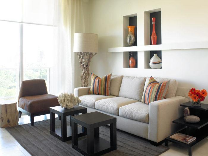 غرفة جلوس بتصميم بسيط وجميلة مكونة من كنبة ومقعد مع ترابيزة خشبية سوداء