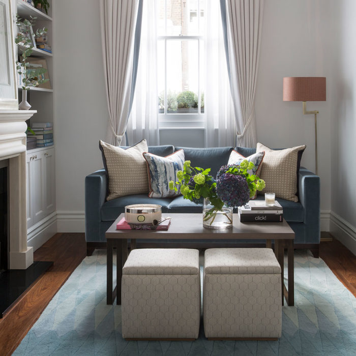 غرفة جلوس بتصميم راقي مكونة من كنبة صغيرة و2 باف وترابيزة خشبية وفازة الورد تعطي منظراً جميل