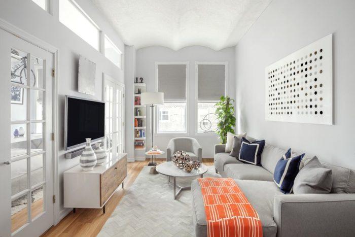 غرفة جلوس بتصميم سيمبل وجميل مكونة من ركنة رمادية ومقعد مع ترابيزة دائرية روعة