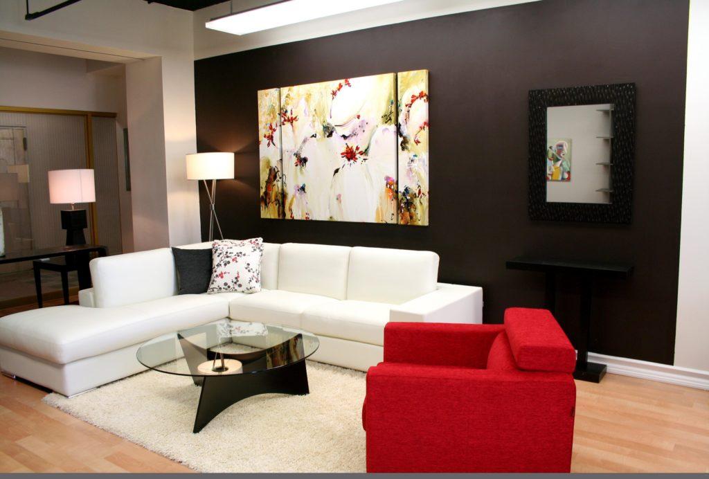 غرفة جلوس بتصميم سيمبل وهادئ مكونة من ركنة بيضاء وكرسي باللون الاحمر مع ترابيزة زجاجية مستديرة