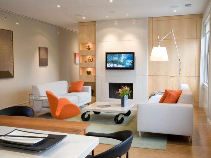 غرفة جلوس بتصميم ناعم مكونة من 2 كنبة بيضاء وتحتوي على وسادات برتقالية مع ترابيزة رائعة