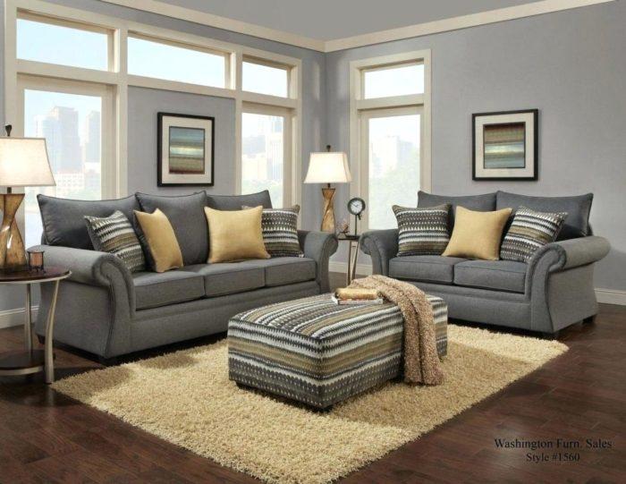 غرفة جلوس مكوة من 2 كنبة رمادية اللون وتحتوي على وسادات منقوشة وباف مستطيل لوضع الاشياء