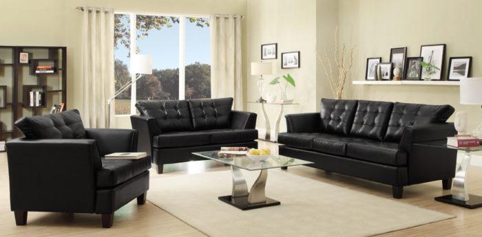 غرفة معيشة باللون الاسود بتصميم شيك جداً مكونة من 2 كنبة وكرسي وترابيزة زجاجية جميلة