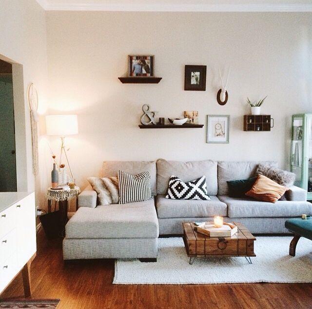 غرفة معيشة بتصميم راقى مكونة من ركنة رمادية وعليها وسادات مننقوشة مع ترابيزة خشبية