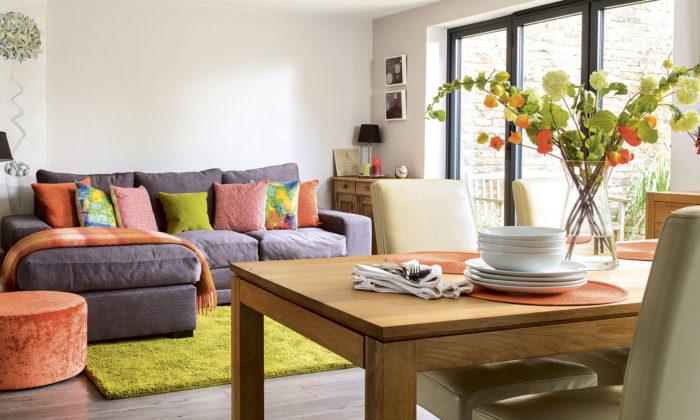 غرفة معيشة شيك جداً مكونة من ركنة باللون الموف ويحتوي على وسادات ملونة وباف دائري برتقالي