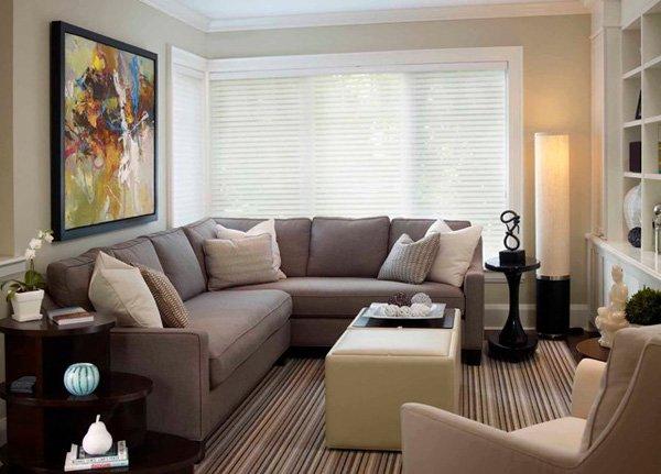 غرفة معيشة صغيرة مكونة من ركنة بيج وكرسي وترابيزة بتصميم بسيط