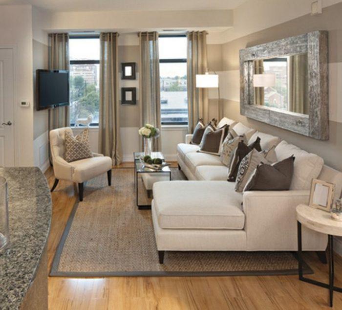 غرفة معيشة مكونة من مقعد وركنة باللون البيج مع ترابيزة زجاجية صغيرة