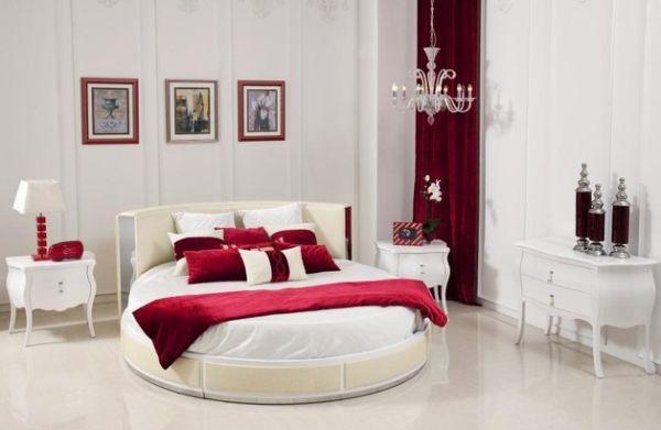 غرفة نوم باللون الابيض مكونة من سرير دائري و 2كمودينو