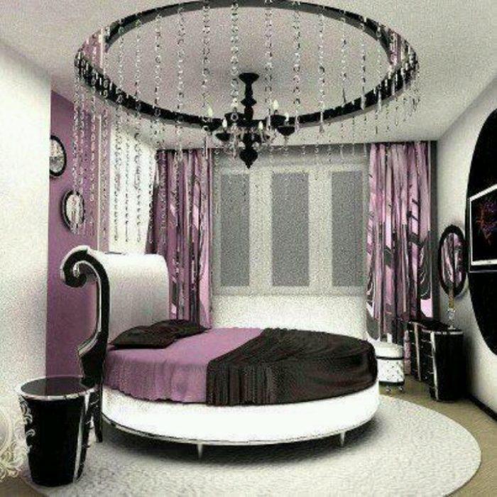 غرفة نوم مكونة من سرير دائري وتسريحة وكمودينو بتصميم رائع