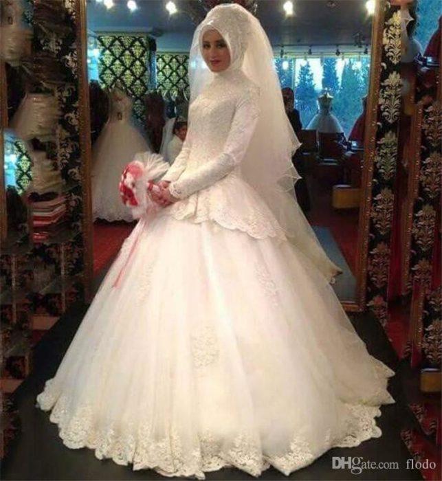 فستان زفاف بأكمام طويلة وتقفيلات أنيقة للعروس المحجبة تبدو كملكة متوجة فى ليلة العمر
