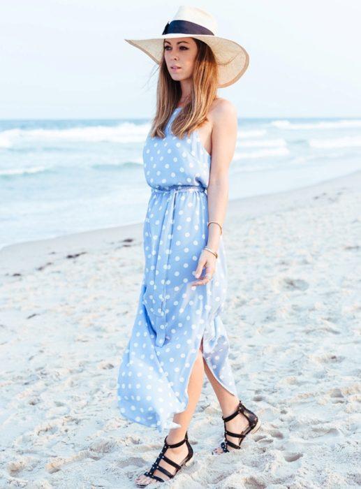 فستان طويل باللون اللبني منقط بأبيض مفتوح من الجانبين مع قبعة تحميكي من الشمس